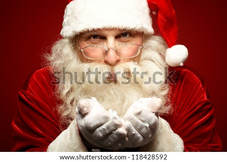 Photo of kind Santa Claus with snow in hands looking at camera
