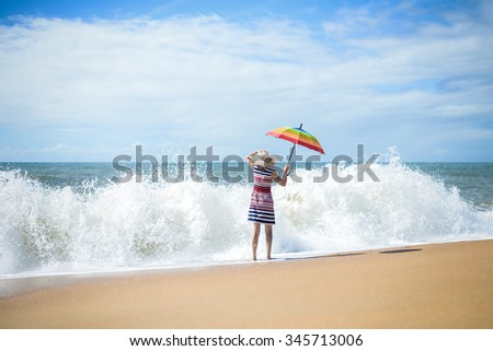 Photo of lady going into foamy wave and holding rainbow color umbrella  looking out for something  on coastline background