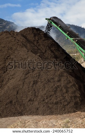 Photo of large amount of compost being produced. - stock photo