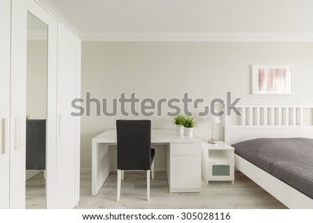 Photo of light cosy bedroom with study area - stock photo