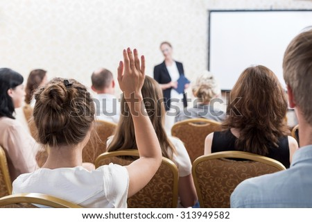 Photo of listener raising hand to ask question during seminar - stock photo