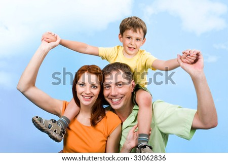 Photo of little boy sitting on parents? shoulders on a blue background