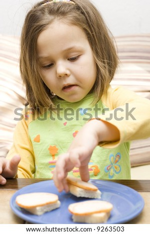 photo of little, cute girl eating a sandwich