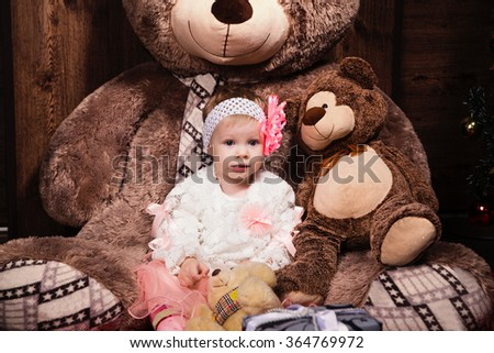 photo of Little cute girl in white dress with big smile Teddy bear.