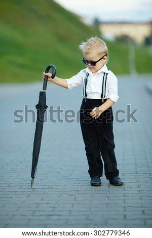 photo of little gentleman with sunglasses outdoors portrait - stock photo