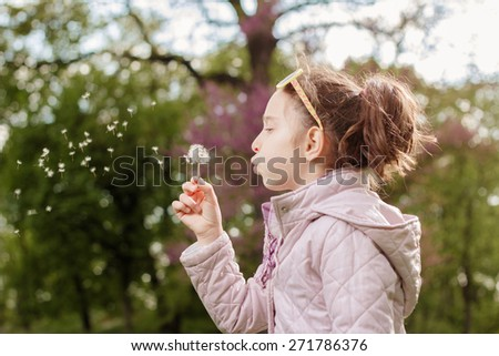 Photo of little girl blowing a dandelion seeds
