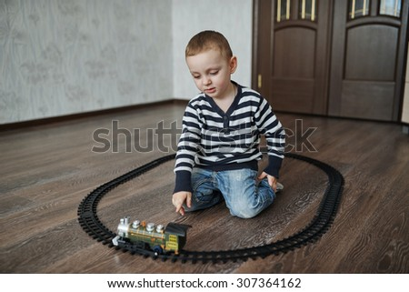 photo of little happy boy builds toy railroad - stock photo