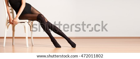 Photo of long slim pretty legs in stylish tights.