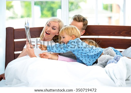 Photo of loving family of four lying on white bed in morning. Family hugging and reading book