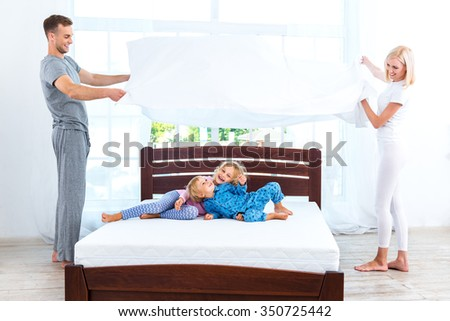 Photo of loving family of four making bed. Young family demonstrating quality of mattress and holding blanket - stock photo