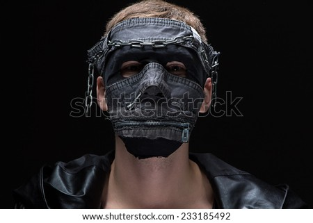 Photo of madman in handmade mask on black background