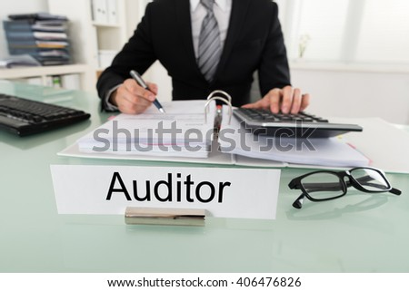 Photo Of Male Auditor Calculating Bill In Office - stock photo