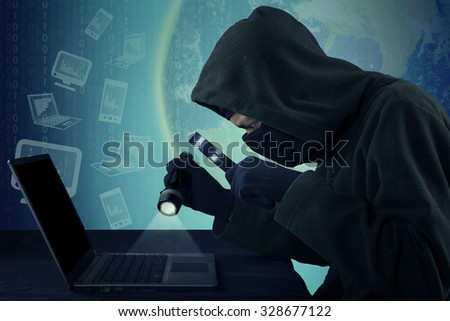 Photo of male thief wearing mask and steal user identity on the laptop while using flashlight and magnifying glass - stock photo