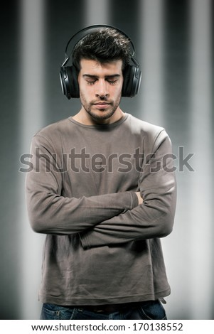 Photo of man who is listening to music while wearing headphones - stock photo