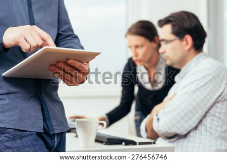 Photo of man working on tablet in the office