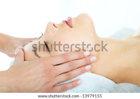 Photo of masseuseâ??s hands doing relaxing massage on young woman's face