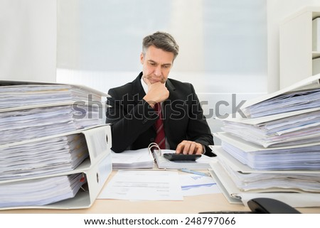Photo Of Mature Businessman Calculating Invoices In Office - stock photo