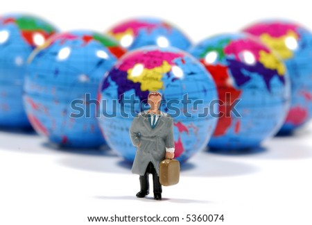 Photo of Minature Globes and a Miniature Man - Business Travel Concept - stock photo