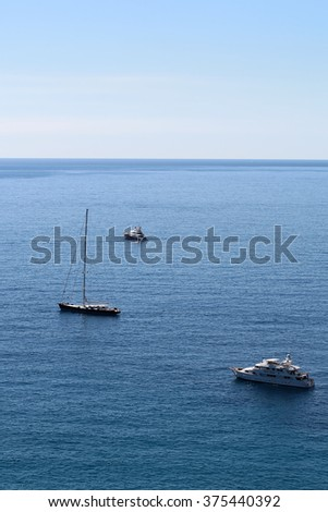 Photo of modern and classic yachts sailing boats vessels offshore in calm blue sea silhouetted against clear sky day time on beautiful seascape background, vertical picture - stock photo