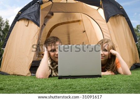 Photo of modern couple lying on green grass and looking at laptop monitor in tent - stock photo