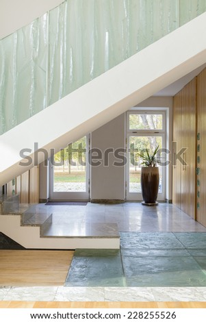 Photo of modern stylish hallway with big stairs