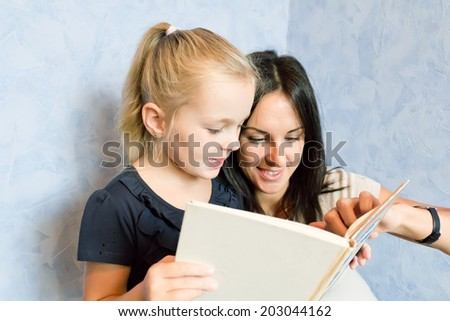 Photo of mother and daughter is younger schoolgirl - stock photo