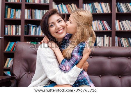 Photo of mother and little daughter. Nice cozy interior with big bookcase. Mother looking at camera and smiling while daughter kissing her - stock photo