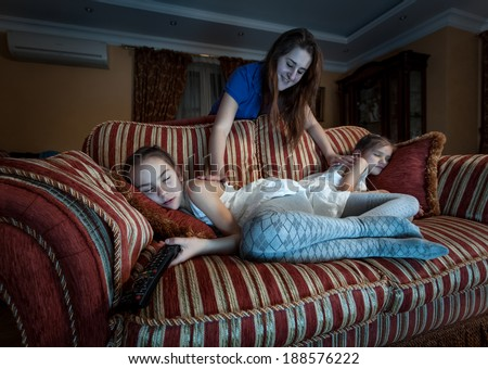 Photo of mother waking up two daughter fell asleep at night while watching TV - stock photo