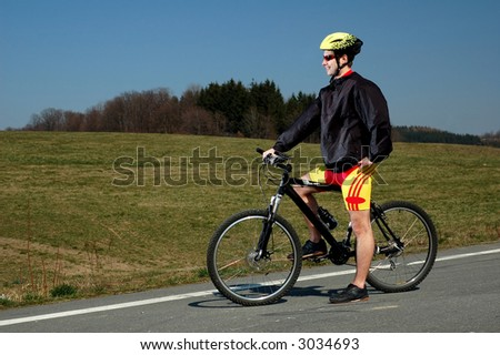 Photo of mountain biker in sporting costume with helmet.