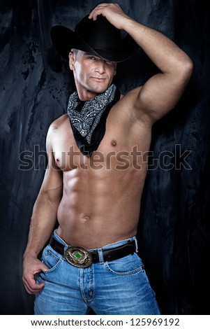 Photo of muscular handsome man posing in a cowboy hat and jeans over the grunge wall. - stock photo
