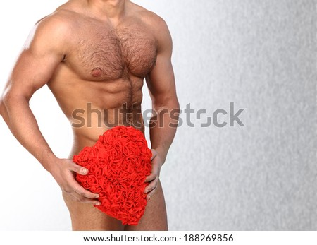 Photo of naked athlete man with strong body, with big red heart in his arms - stock photo