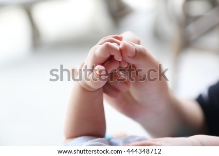 Photo of newborn baby feet and hand in soft focus