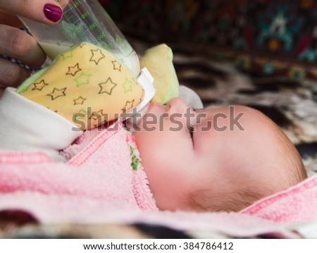 photo of newborn baby sucking bottle - stock photo