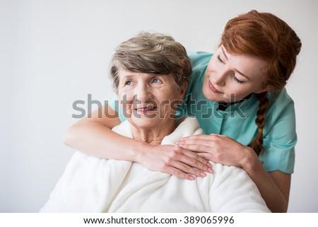 Photo of nurse and senior female patient on geriatric ward - stock photo