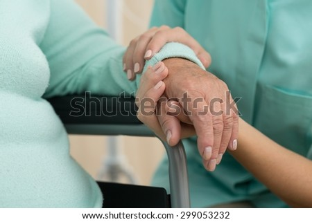 Photo of nurse supporting old woman on wheelchair - stock photo