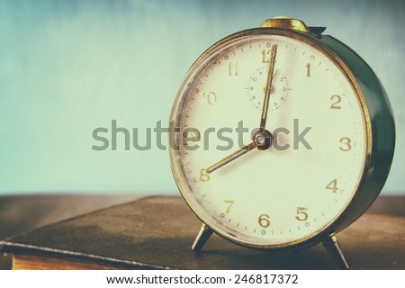 photo of old alarm clocl over wooden table, with faded retro effect - stock photo