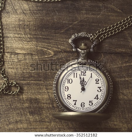 Photo  of old vintage pocket watch on rustic wood.  Retro filtered image - stock photo