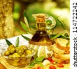 Photo of olive oil still life, healthy organic salad dressing, lebanese cuisine, glass bottle with olive oil, marinated olives and bread on tray in garden, homemade food, harvest season - stock photo