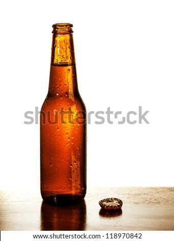 Photo of open beer glass bottle with lid on the table isolated on white background, alcohol beverage, cold bubbles drink, amber ale, brew pub, german beer festival, tavern, fresh lager - stock photo
