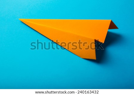 Photo of orange origami paper airplane on blue paper background - stock photo