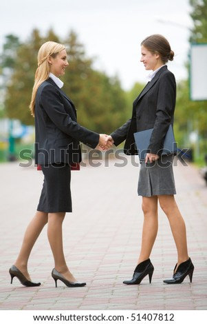 Photo of partnership - business women shaking hands at meeting