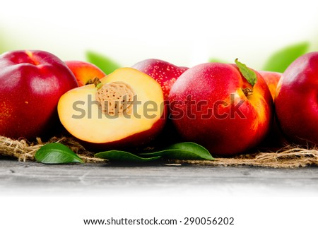 Photo of peaches with slice and leaves on burlap with white space