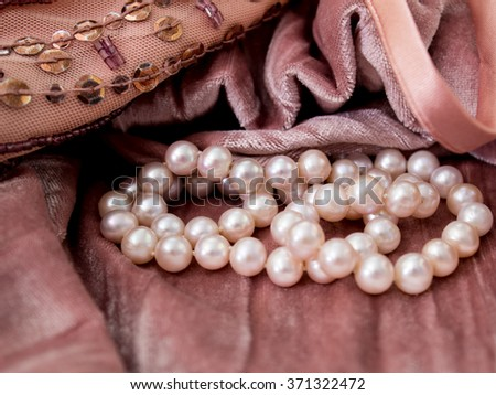 Photo of pink pearls on pink velvet fabric background with sequins and beads