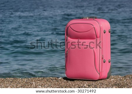 Photo of pink suitcase of a tourist on pebbles with the sea near by - stock photo