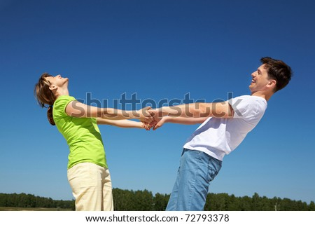 Photo of playful couple holding each other by hands with their arms stretched against blue sky - stock photo