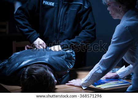 Photo of policeman arresting suspect after interrogation on police station - stock photo