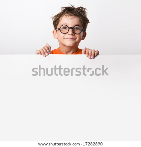 Photo of positive schoolkid behind partition looking at camera with smile - stock photo