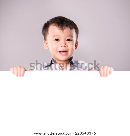 Photo of positive schoolkid behind partition looking at camera with smile. Portrait of a little boy in spectacles with white board. Isolated over white background.  - stock photo