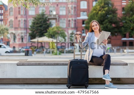 Photo of pregnant businesswoman reading the newspaper on a bench