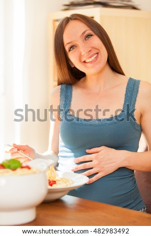 Photo of pregnant woman eating huge portion of pasta with tomato sauce